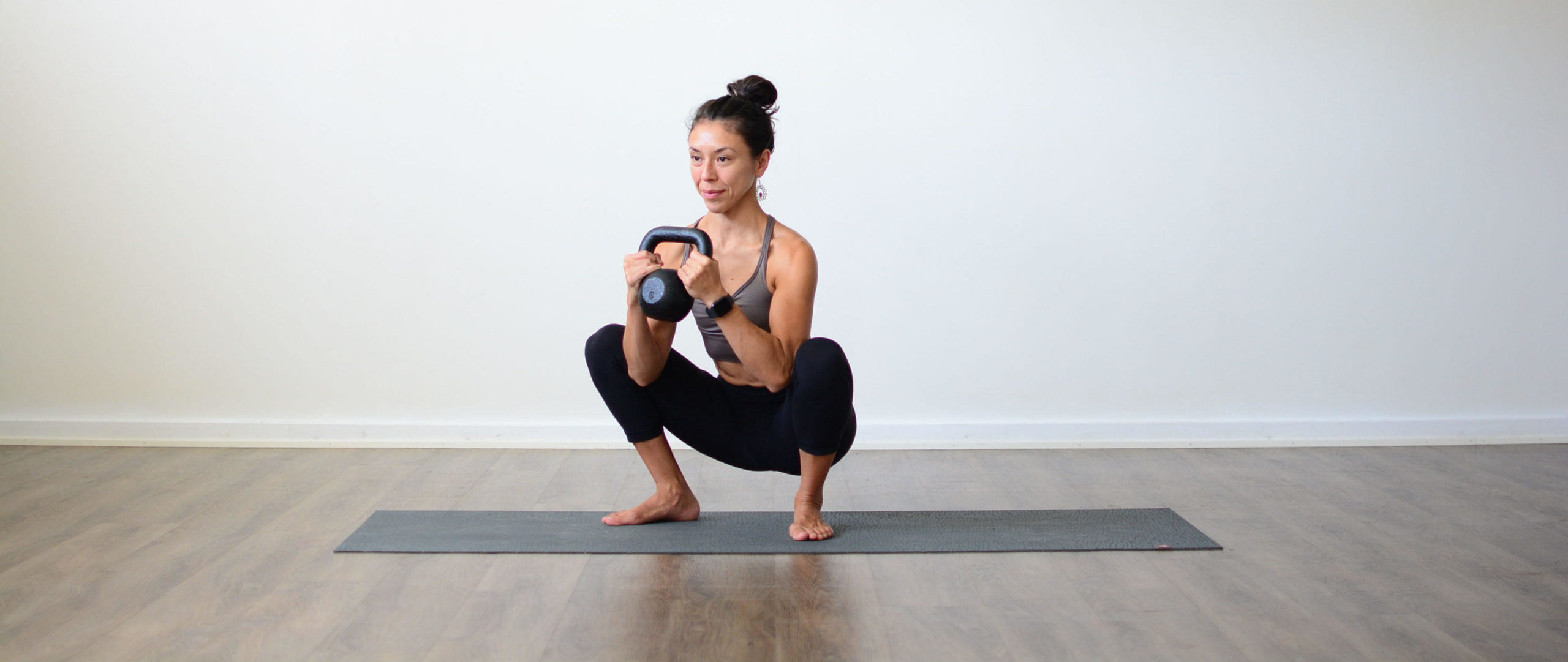 Lizette Pompa sitting in a squat with a kettlebell for Strength Training to Complement Yoga