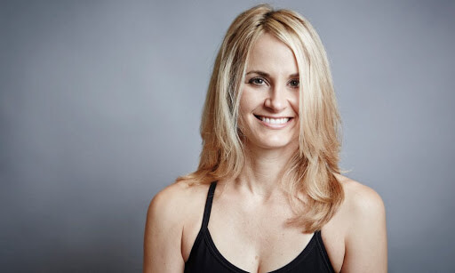 a blond woman wearing a black tank top while smiling