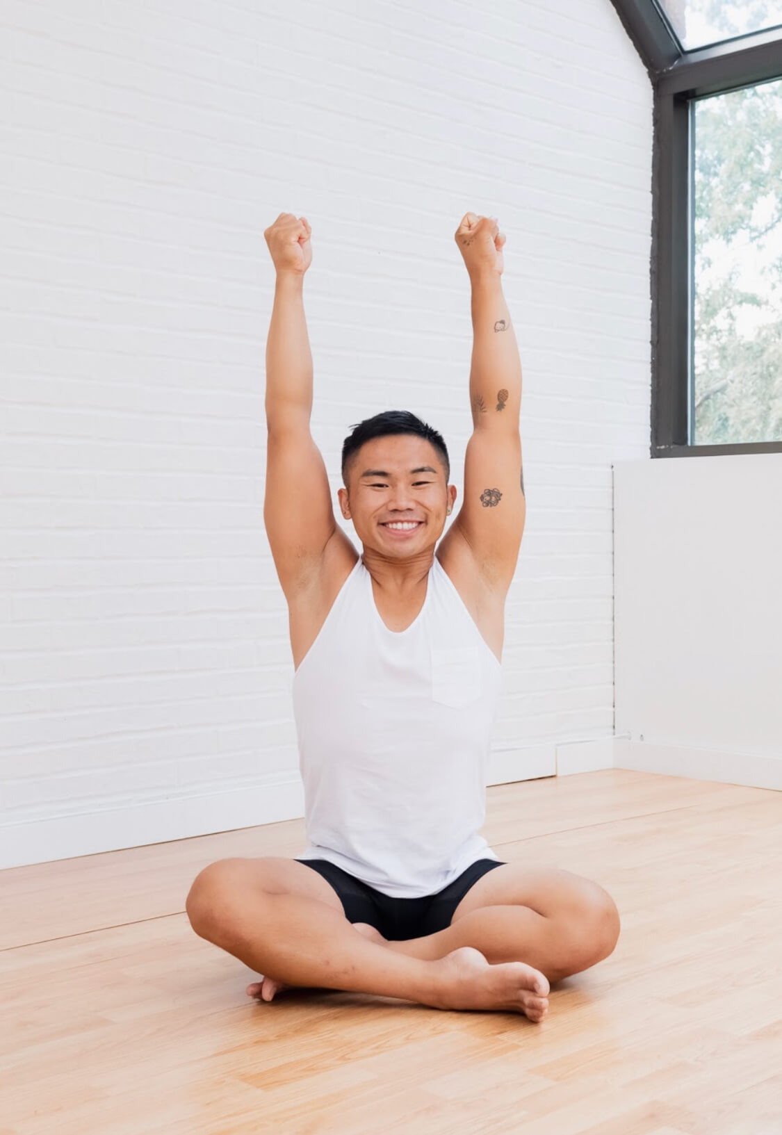 Chris Nguyen on a yoga mat performing a yoga pose with his leg wrapped around his back.